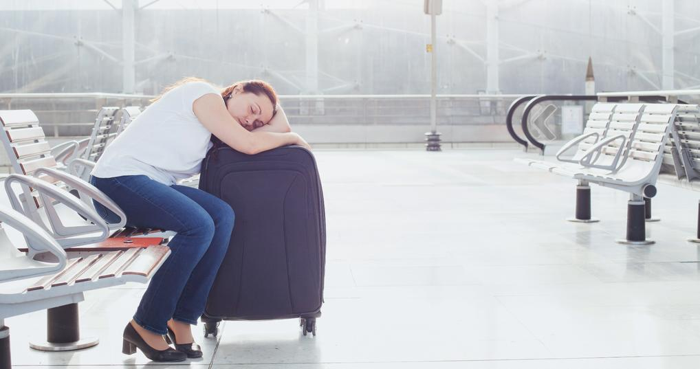 Woman sleeping on luggage at airport during layover