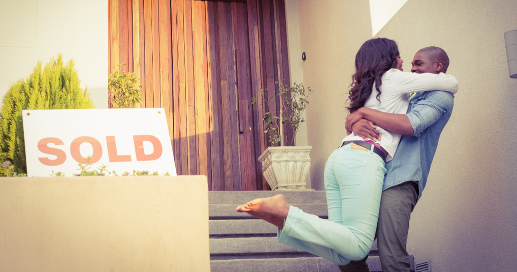 Happy couple embracing in front of a newly sold home