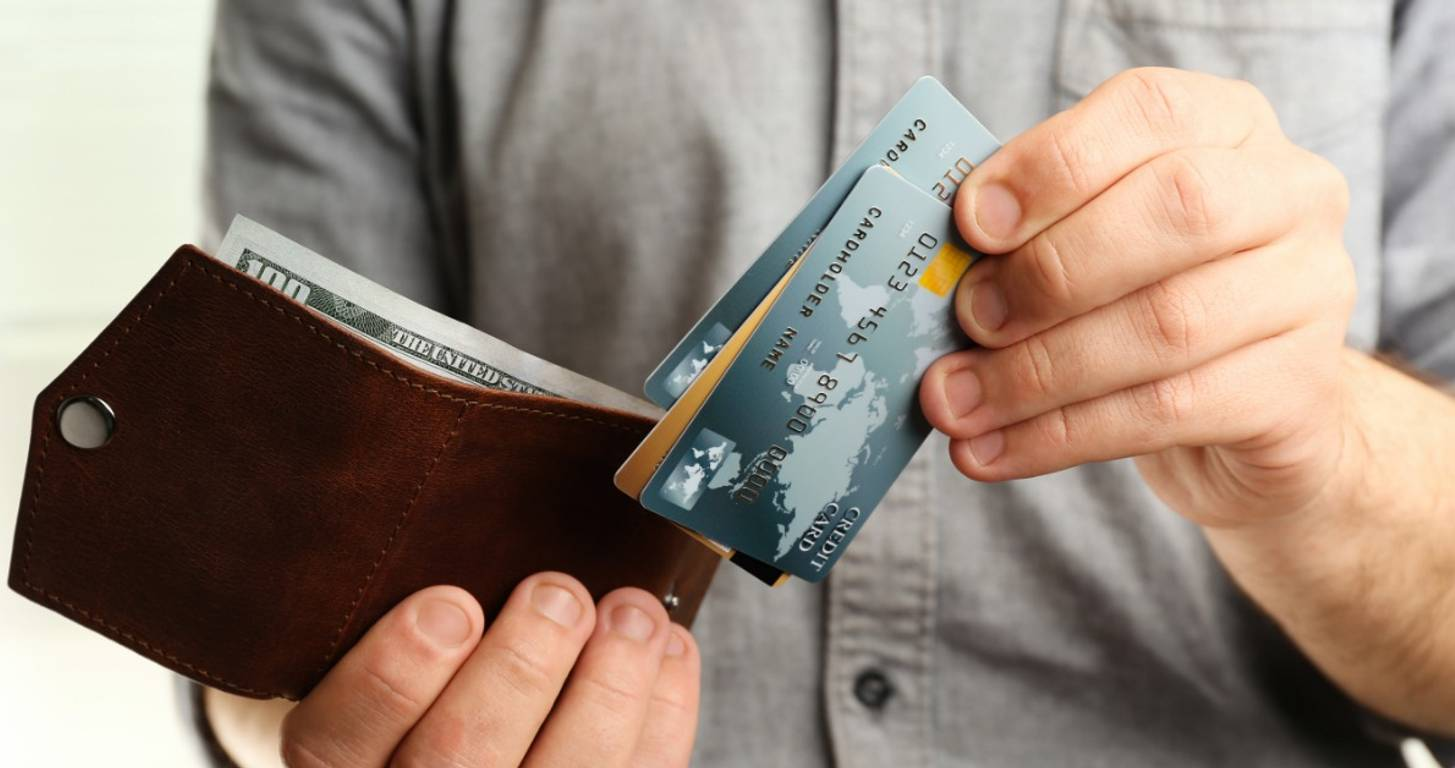 Man holding wallet with multiple credit cards
