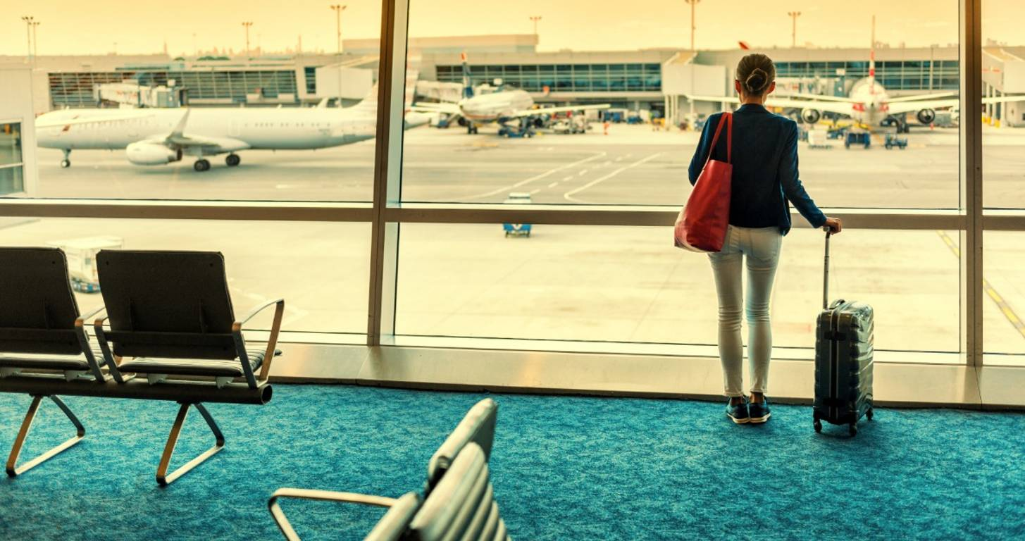 Woman standing in an airport with luggage