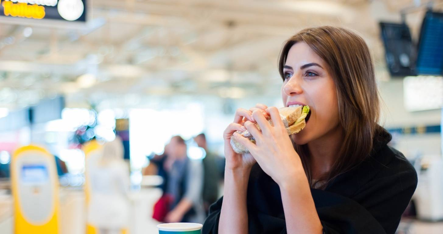 Woman eating coffee and sandwich at the airport