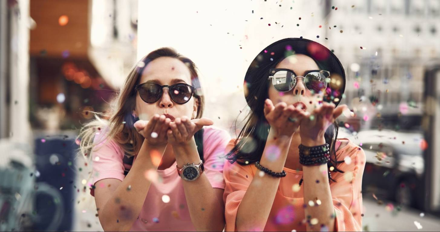 Cheerful women blowing confetti from their hands