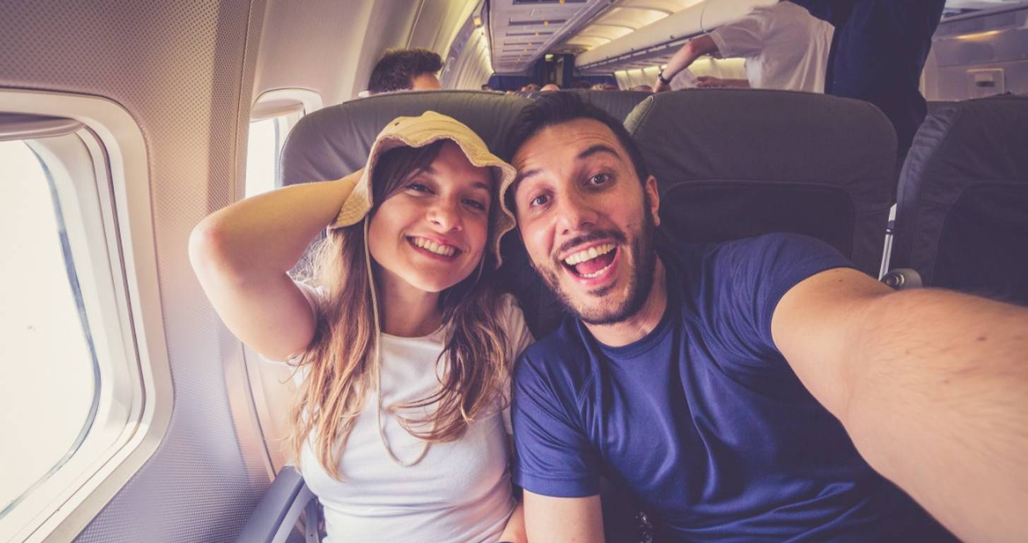 Young couple taking a selfie on an airplane
