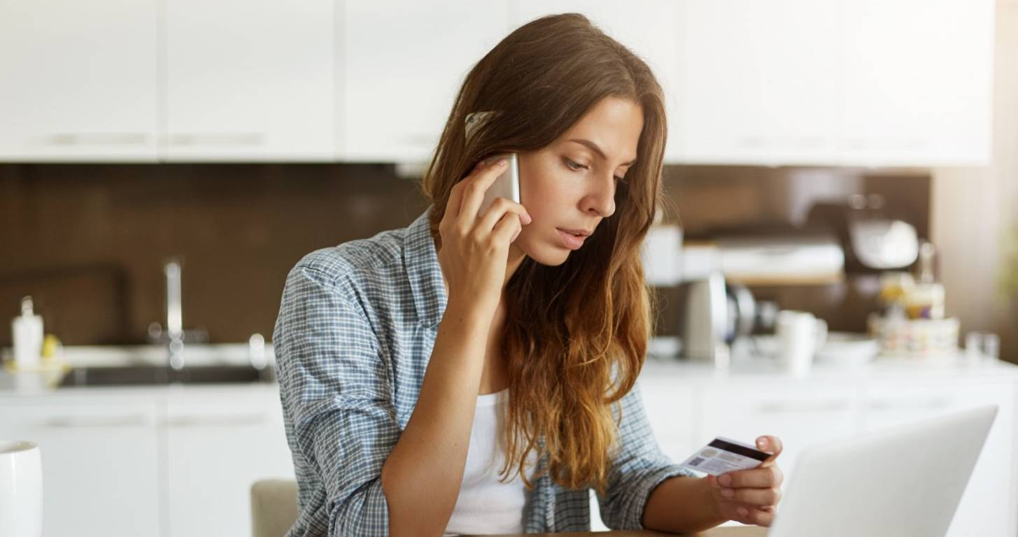 Woman on the phone looking at her credit card
