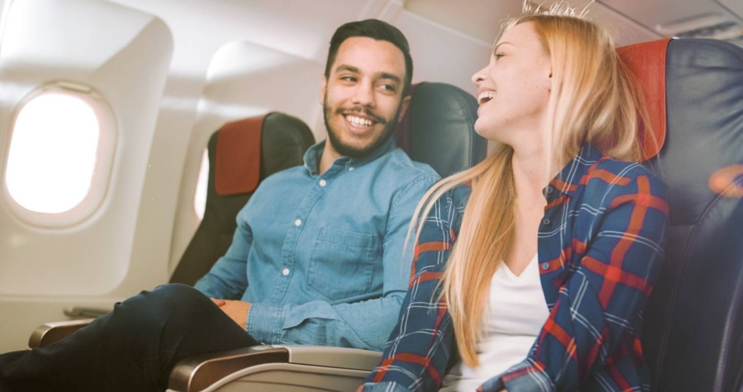 Young couple laughing together on an airplane