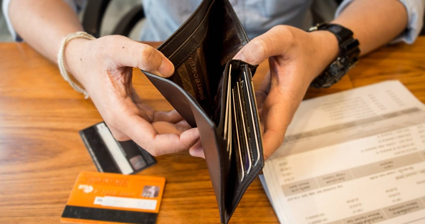 Man holding empty wallet with credit card bill