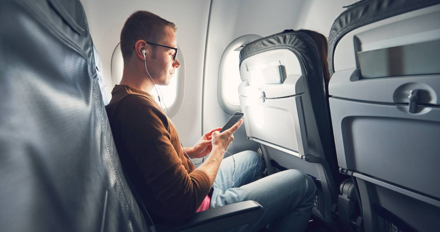 Young man looking at his phone on an airplane
