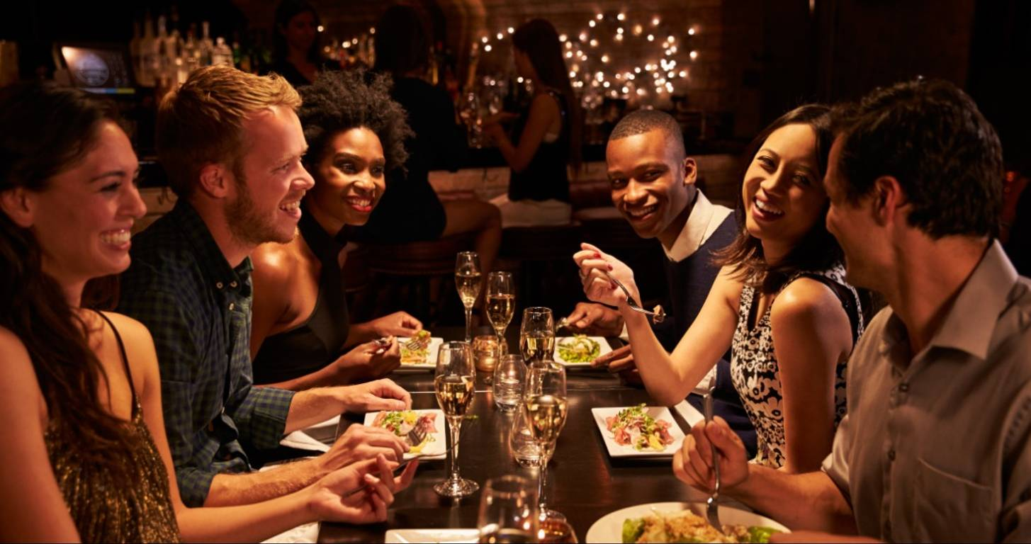 Group of friends at a restaurant using a dining rewards program