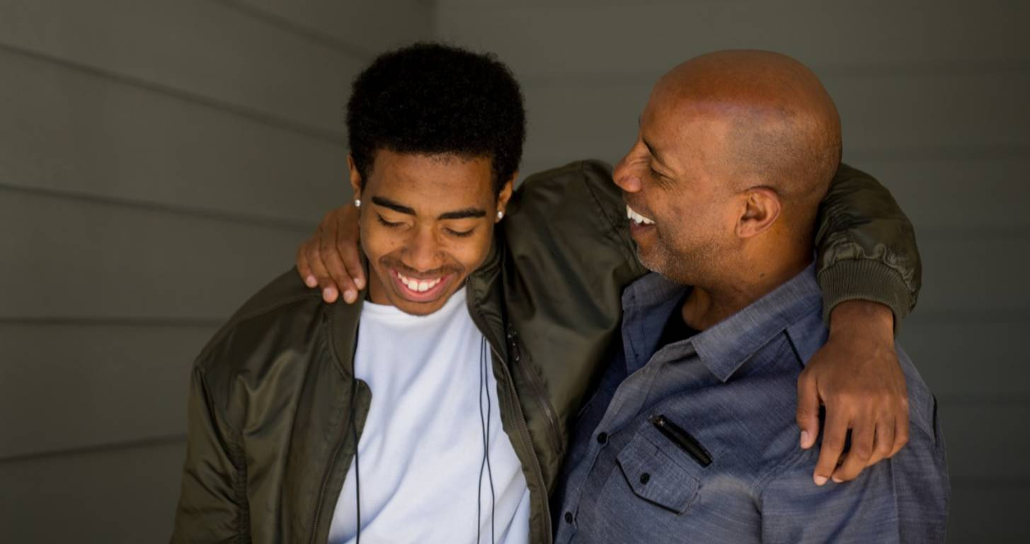 Father and teenage son laughing