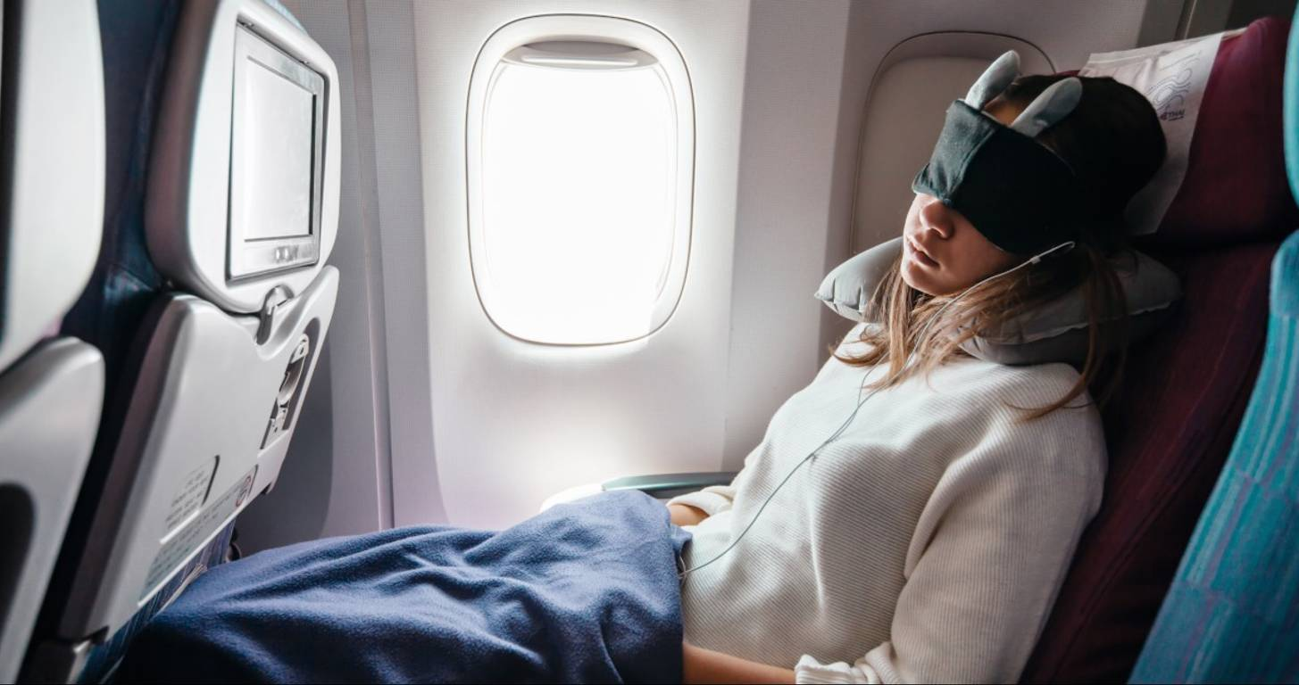 Woman with eye mask sleeping on airplane
