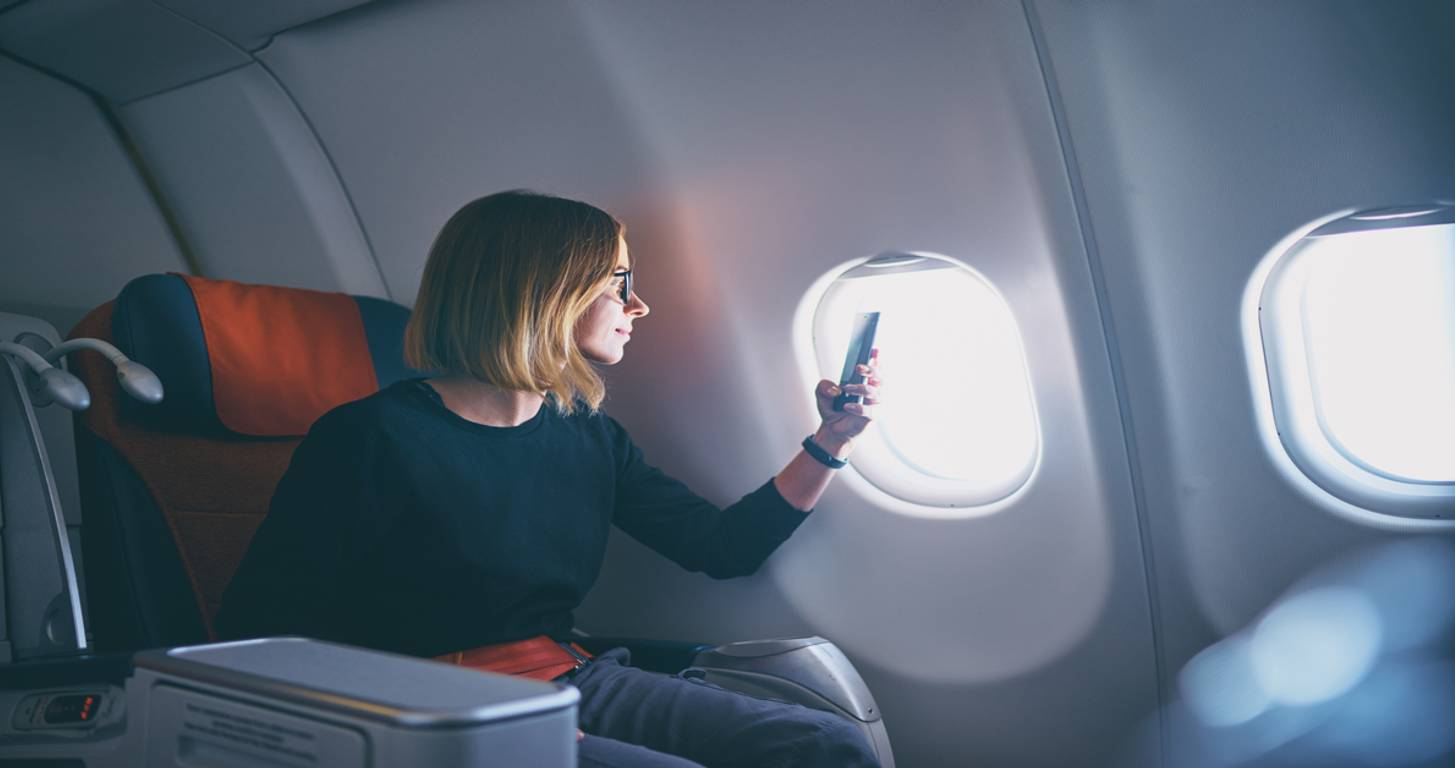 woman on smartphone flying first class