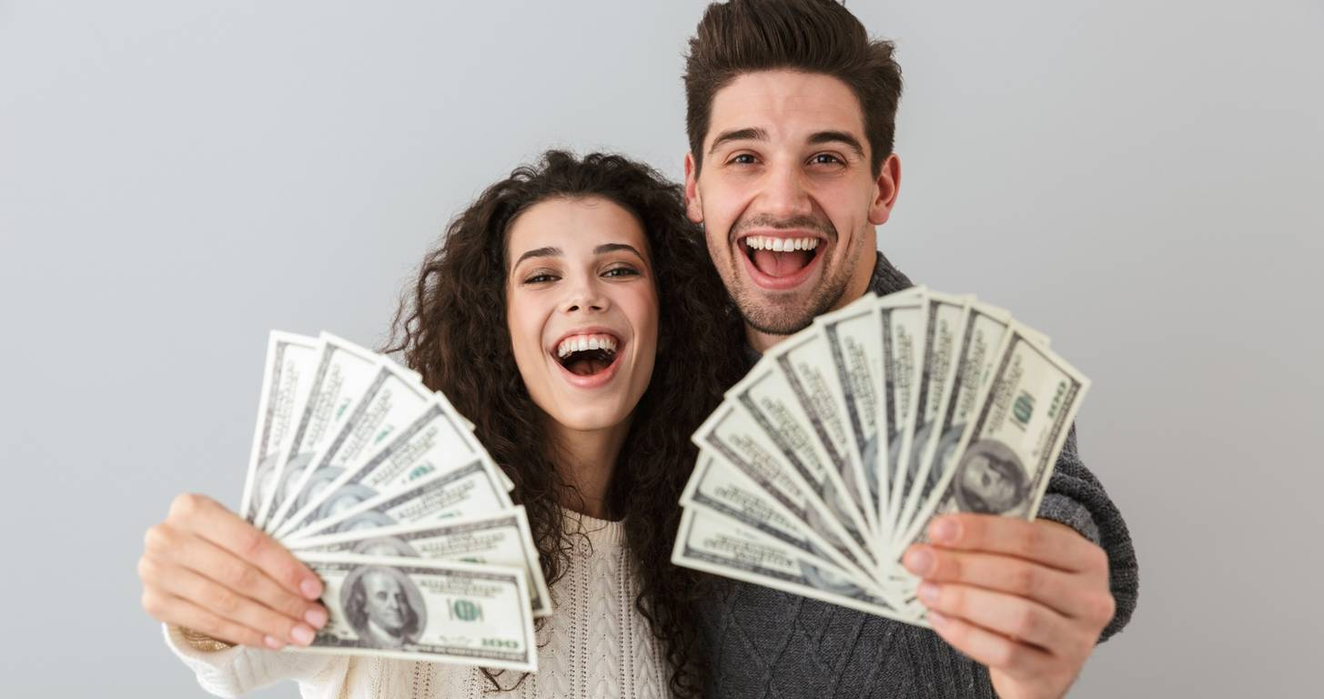 Enthusiastic couple holding money