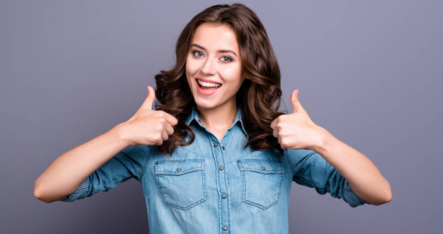 Smiling woman giving two thumbs up