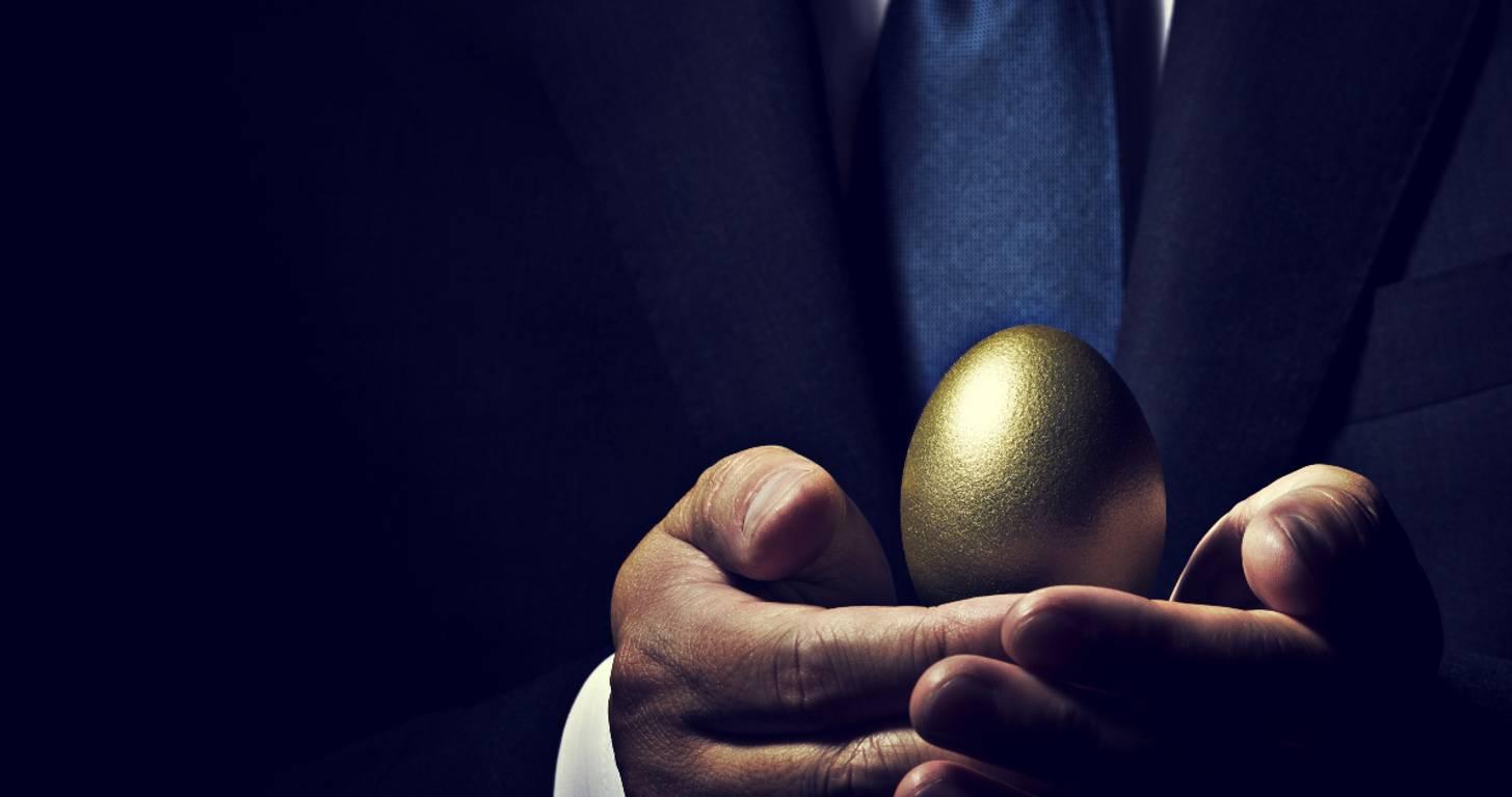 man holding gold nest egg representing wealth