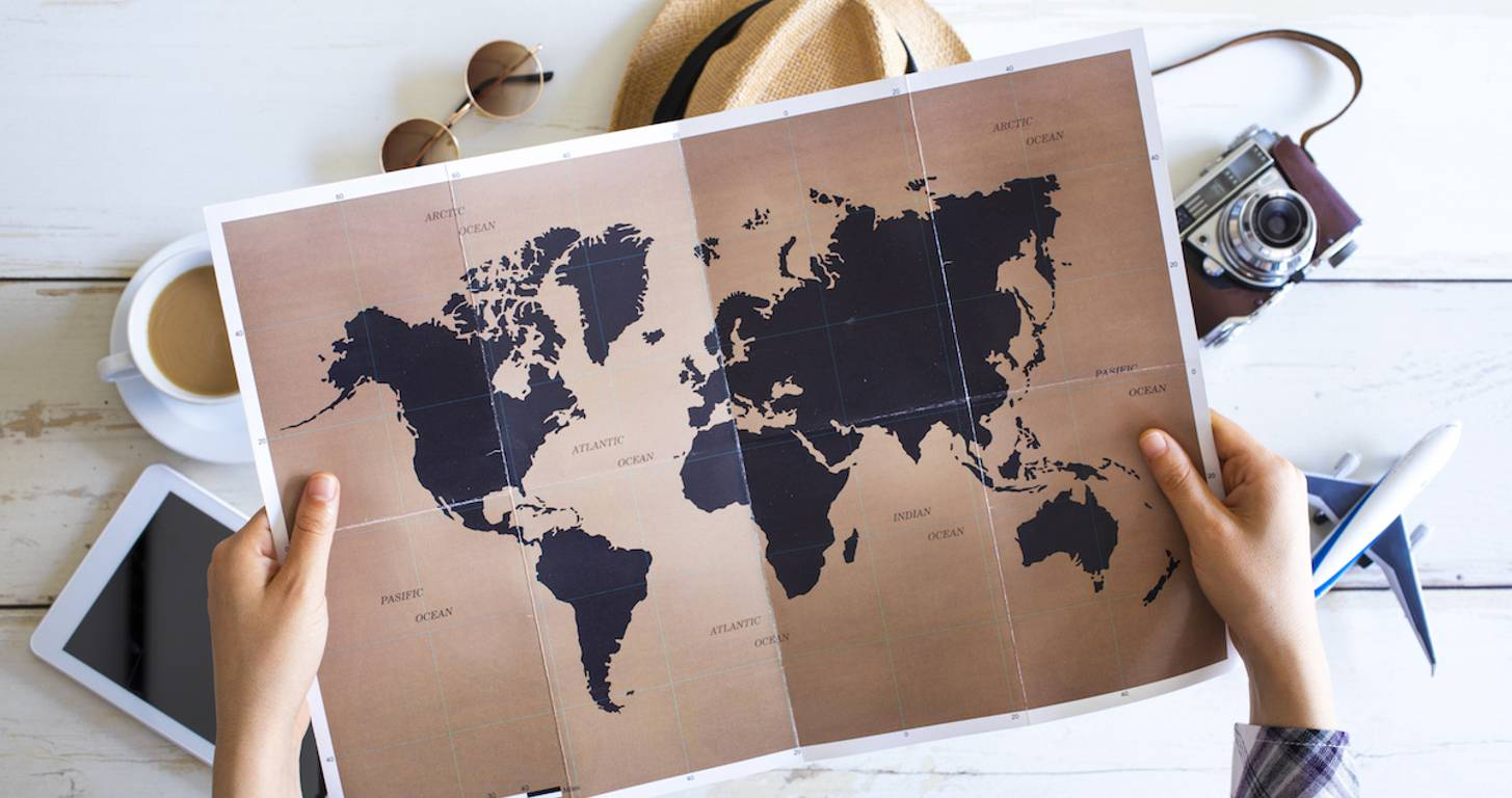map of the world in a person's hands with a toy plane, camera, coffee and tablet surrounding the brown and black map