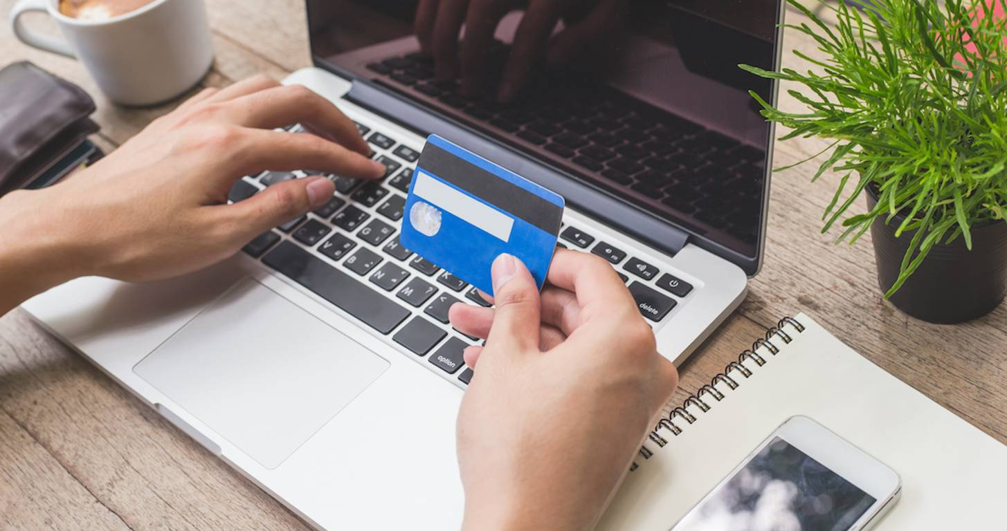Person with laptop holding credit card