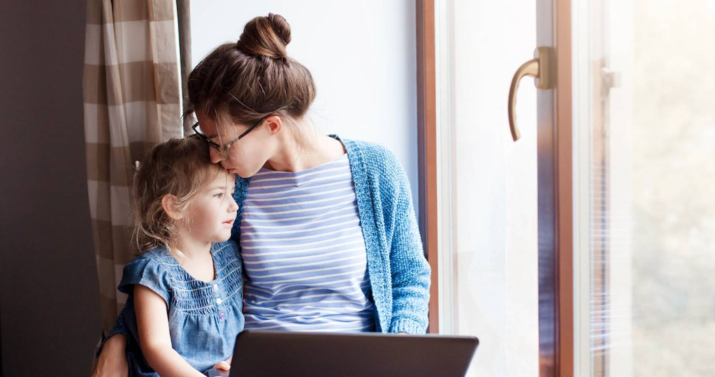 Mother and child sitting in front of laptop