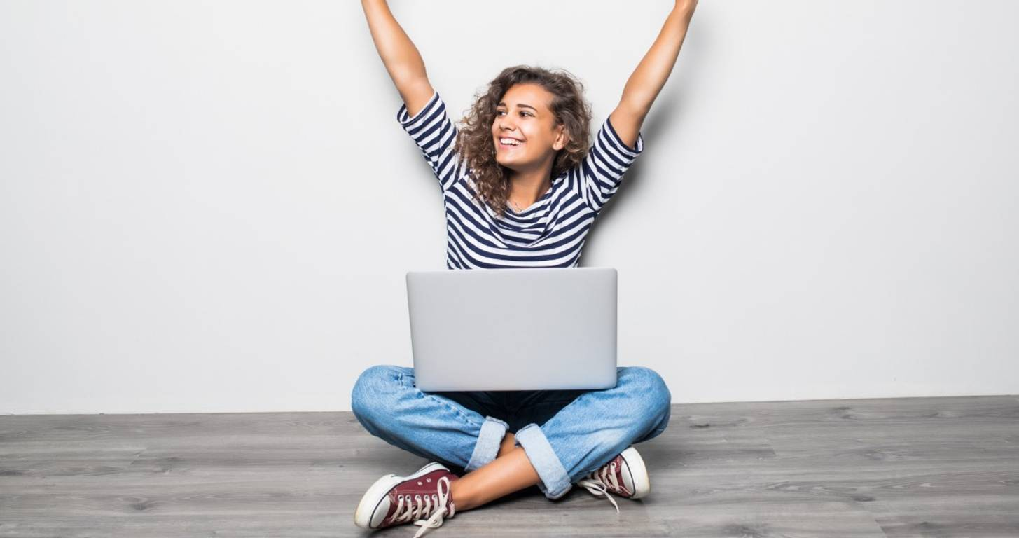 woman with laptop arms in air celebrating
