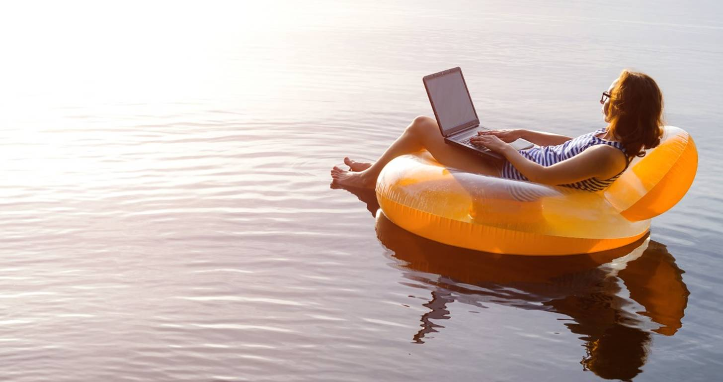 woman floating in lake with laptop
