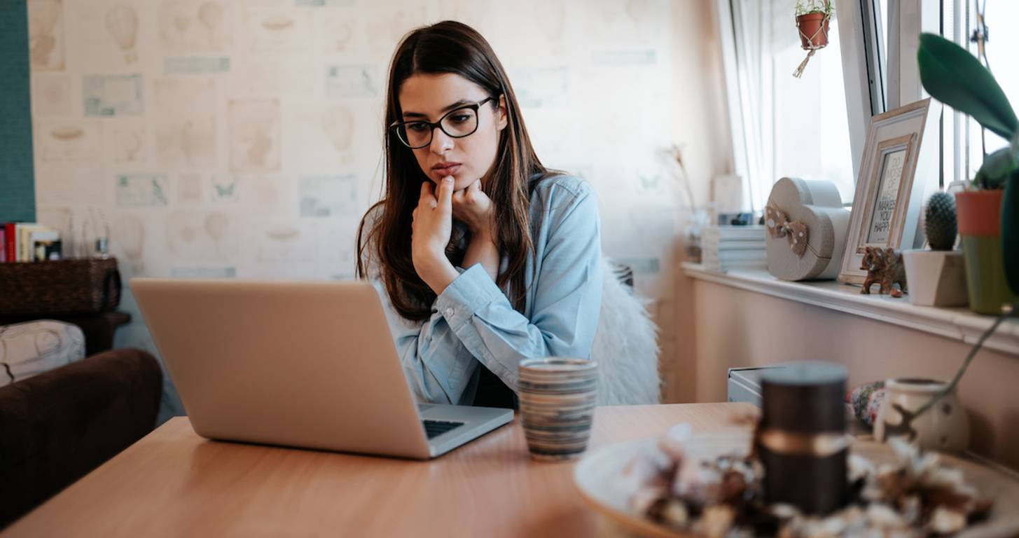 Pensive woman looking at laptop