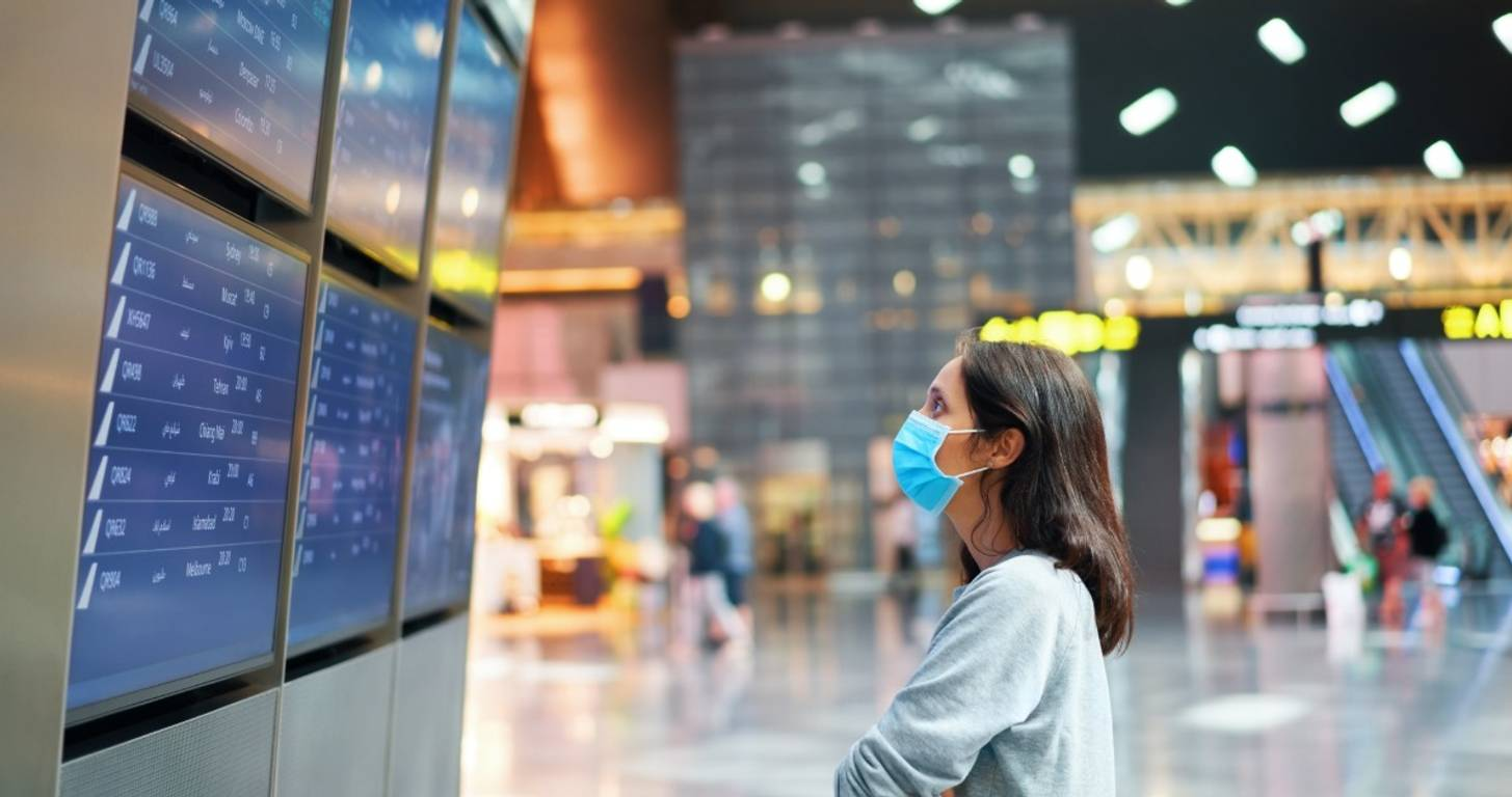 woman looking at flight status at airport