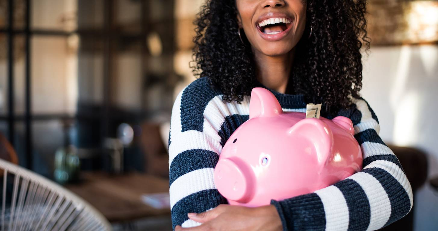 Smiling woman holding piggy bank
