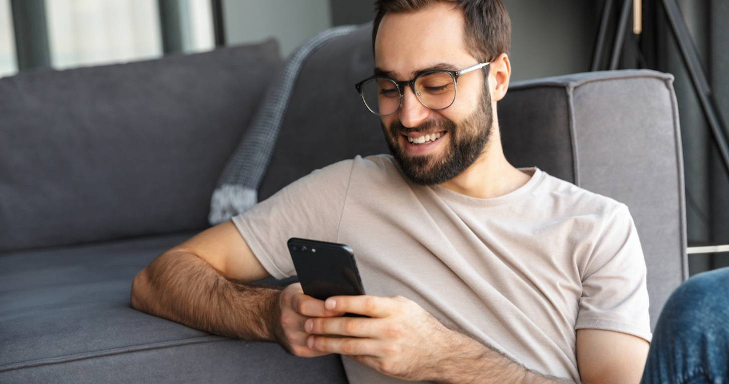 Smiling man typing on smartphone