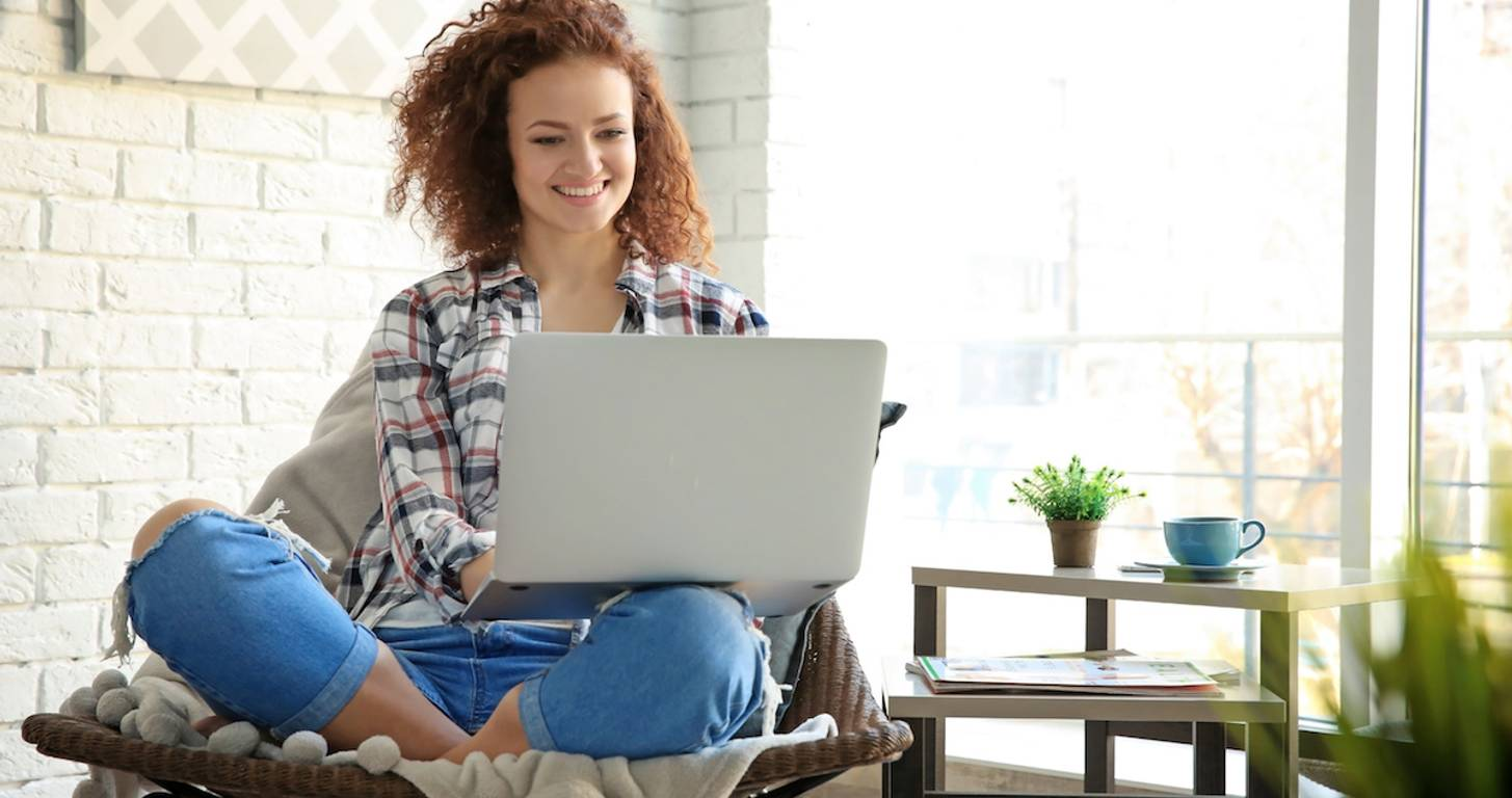Happy woman at home with laptop