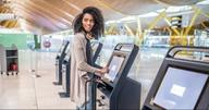 Smiling woman using check-in machine at airport