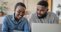 Smiling couple looking at laptop