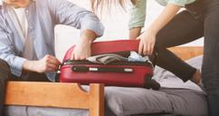 couple stuffing suitcase to avoid baggage fees