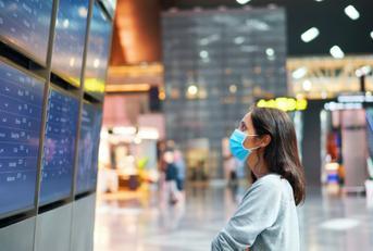 woman looking at flight status at airport