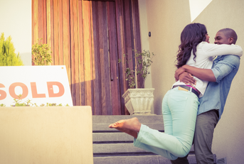 Happy couple embracing in front of newly sold home