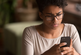 Young Black woman frowning at phone, worried