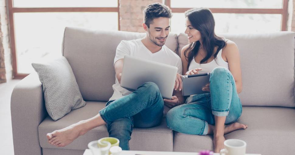 Cheerful young couple using a laptop and tablet at home