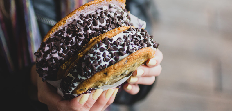 Hands holding two chocolate chip cookie ice cream sandwich from Mix-it-Up at Knott's Berry Farm